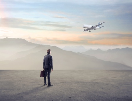 business briefcase: Businessman watching an airplane in a wasteland