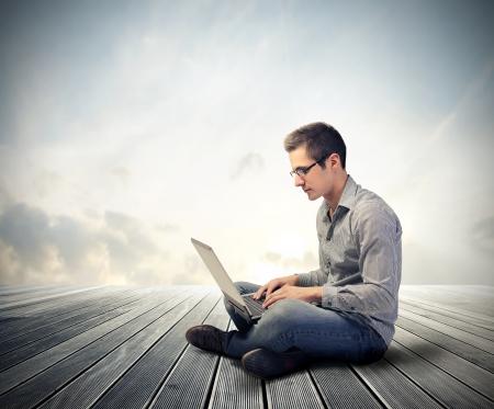 using computer: Man using his laptop computer
