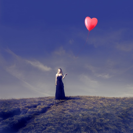 Elegant blonde girl holding a heart shaped balloon in a wasteland photo