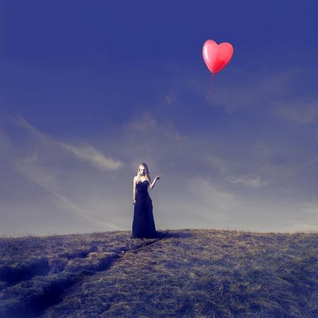 palloncino cuore: Elegante ragazza bionda in possesso di un palloncino a forma di cuore in una terra desolata
