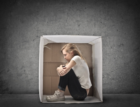 Blonde girl crouched in a box photo