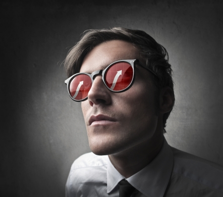 Fashionable man posing with a pair of sunglasses with red lens