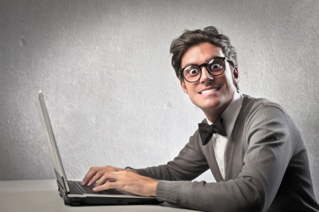 nerd glasses: Fashionable man forcedly smiling while using a laptop computer