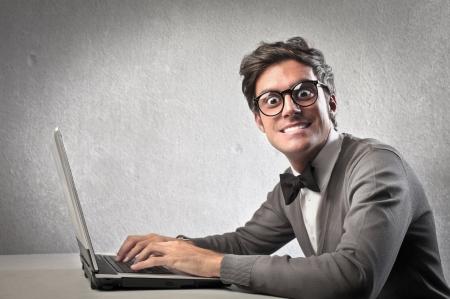 Fashionable man zwangsweise lächelnd, während mit einem Laptop-Computer