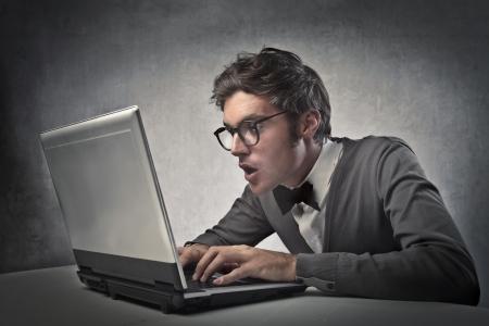 asombro: Hombre de moda sorprendente mientras se utiliza un ordenador portátil