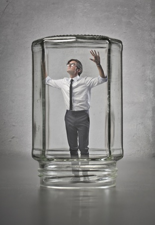 Businessman trapped in a glass container photo