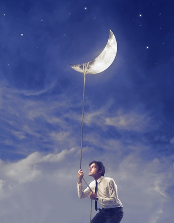 careerist: Businessman holding the moon with a rope