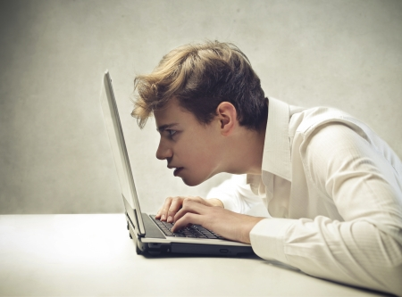 aghast: Boy looking very close to the monitor of his laptop