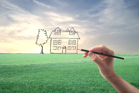 house in hand: Hand drawing a house in a large grace field Stock Photo