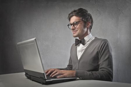 Fashionable man using a laptop computer photo