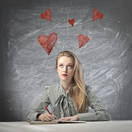 Beautiful blonde girl thinking the love while writing photo