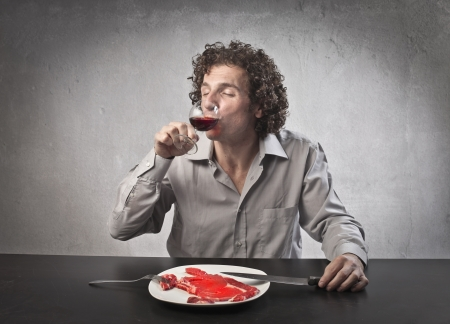flesh: Man drinking a glass of wine while eating a steak