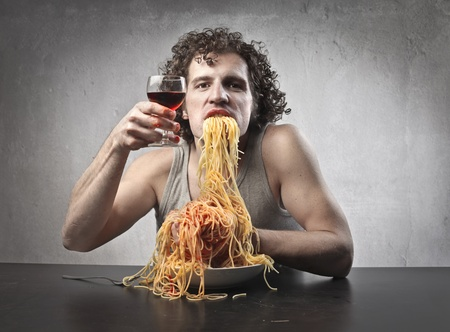 dirty man: Man gorging of spaghetti and drinking red wine Stock Photo