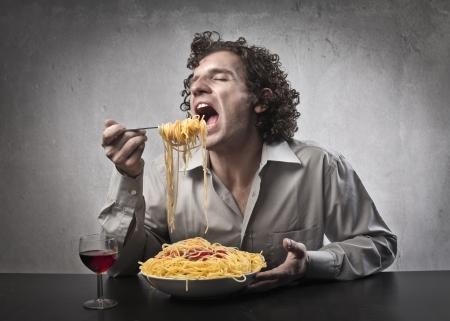 fork glasses: L'uomo mangia gli spaghetti con salsa di pomodoro rosso