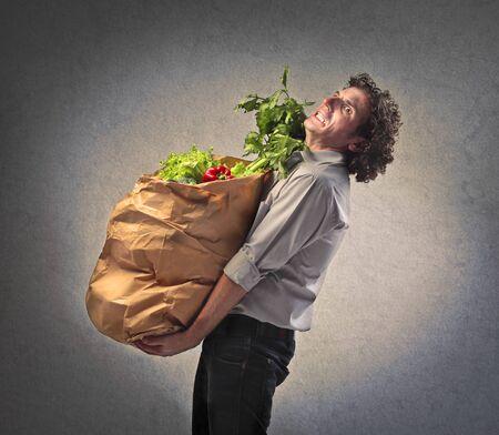 hombre pobre: Hombre que sostiene una lucha bolsa de papel llena de verduras