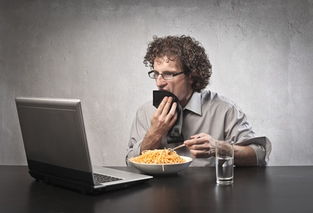 Man eating while using a laptop computer photo