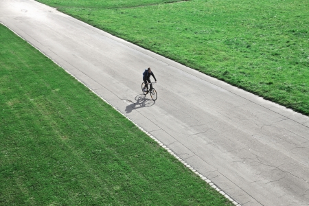 Man cycling on a long road Stock Photo - 15662588