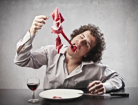 gorging: Man gorging with a steak