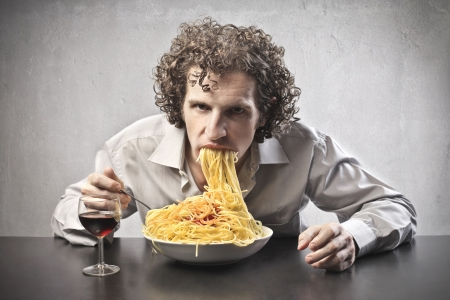 Man gorging of red spaghetti and drinking red wine