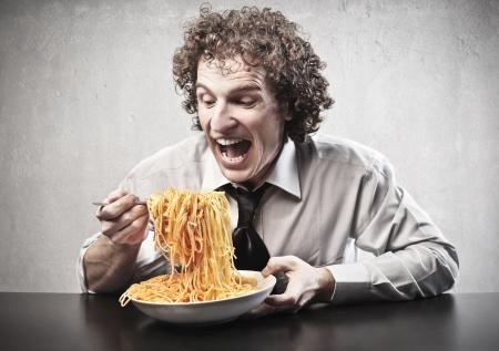 spaghetti dinner: Hungry businessman eating red spaghetti
