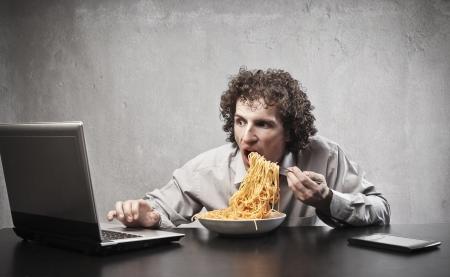 Homme d'affaires mangeant tout en utilisant un ordinateur portable