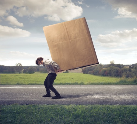 work hard: Businessman holding on his shoulders a large box