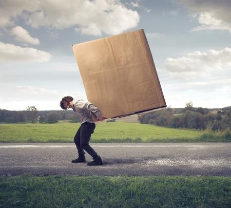 De negocios que sostiene sobre sus hombros una gran caja