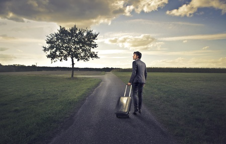 fork in the road: Businessman with his luggage on a long road of countryside Stock Photo