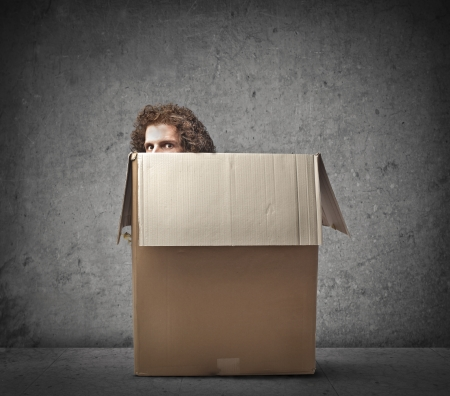 burrow: Man hiding behind a box