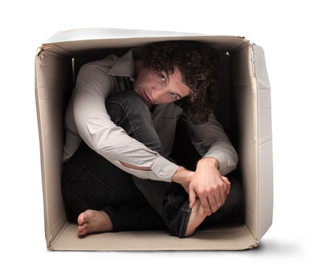 crouched: Man crouched in a box holding one of his feet
