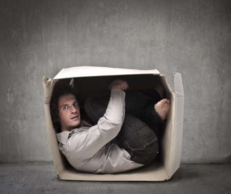 trapped: Man crouched in a box Stock Photo