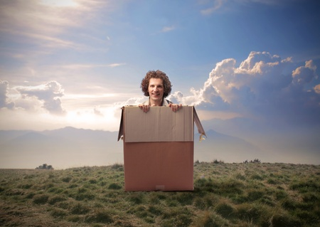 coming out: Man coming out from a box in a wasteland