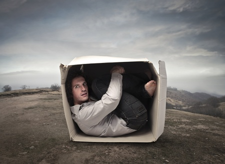 confined: Man crouched into a box in a wasteland Stock Photo