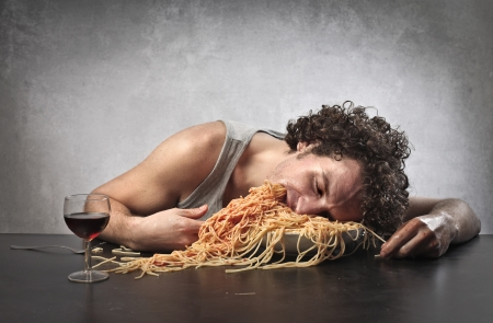 too much: Man passed out from eating too much spaghetti Stock Photo
