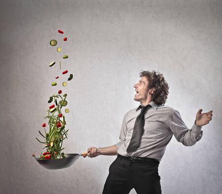 negocios comida: Empresario cocinar algunas verduras con una sart�n