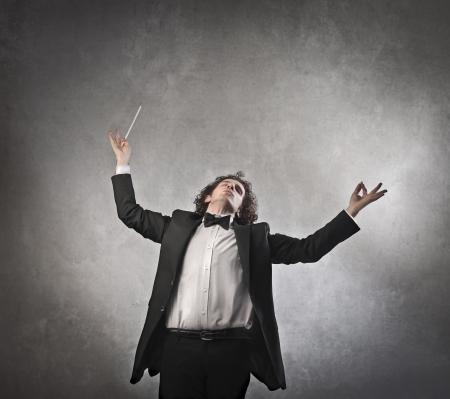 orquesta: El hombre con vehemencia la realizaci�n de una orquesta Foto de archivo