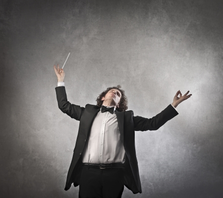 conductor: Man conducting vehemently an orchestra Stock Photo