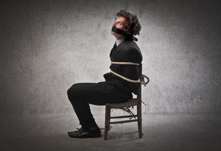 kidnapping: Businessman tied to a chair and gagged Stock Photo