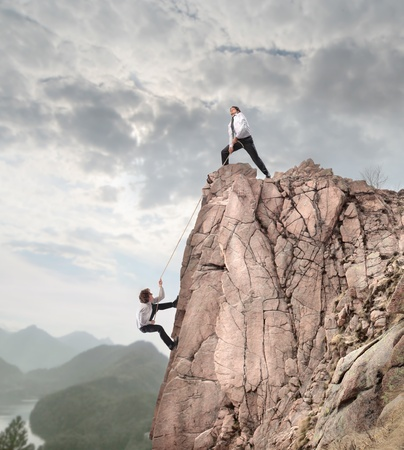 Businessman on the top of a rock helping another businessman to climb it photo