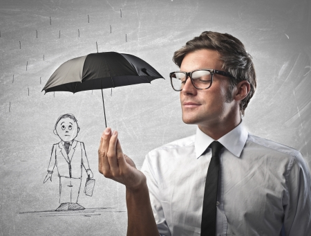 business help: Businessman protecting  with a black umbrella another businessman drawn on a white a wall