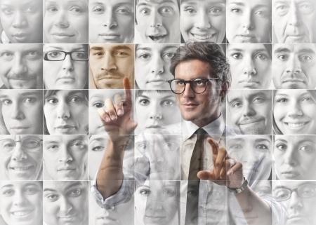 businessman touch screen with virtual faces Stock Photo - 17281498