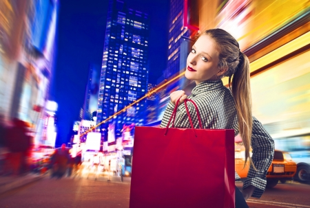 woman night: Beautiful blonde girl holding a red shopping bag in New York Stock Photo