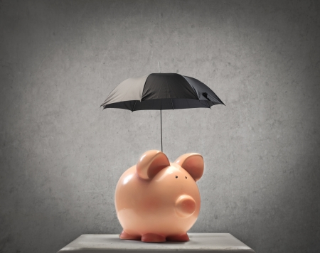 money box: Piggy protecting itself with a little black umbrella Stock Photo