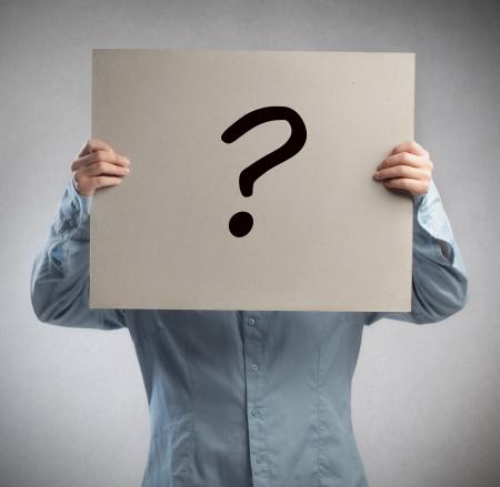 dudas: Hombre que sostiene una cartulina en la que se dibuja un signo de interrogación