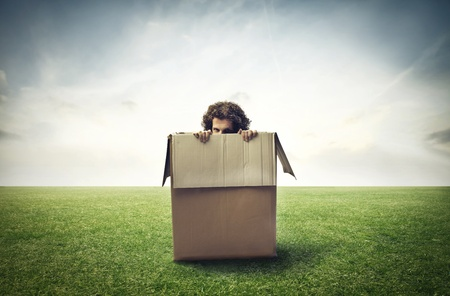 claustrophobic: Man hiding in a box on a large grace field