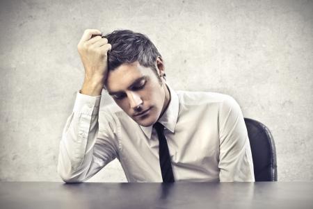 cara triste: Oficinista cansado apoyado en su escritorio Foto de archivo