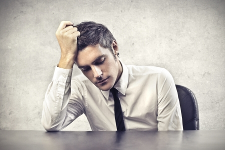 sad businessman: Tired office worker leaning on his desk Stock Photo