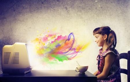 Niño, durante el desayuno, mirando una televisión de la que sobresalen los colores Foto de archivo - 15922094
