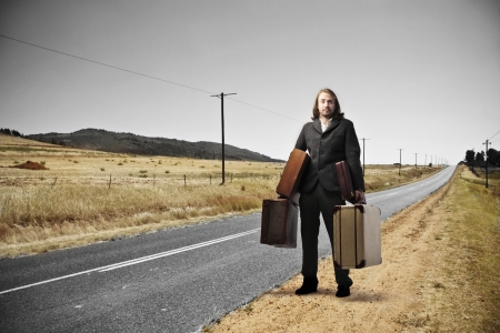 Man with blonde long hair holding some suitcases on a long\ road of countryside