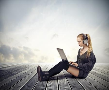 oir: Hermosa chica rubia con un ordenador port�til y escuchar la m�sica Foto de archivo